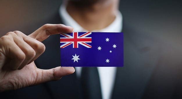 Businessman holding card of australia flag