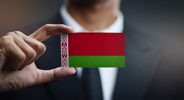 Businessman holding card of belarus flag