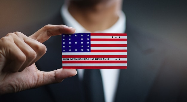 Businessman holding card of bikini atoll flag