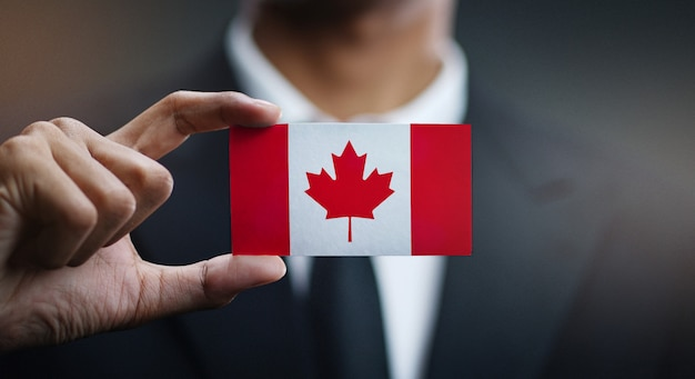 Businessman holding card of canada flag