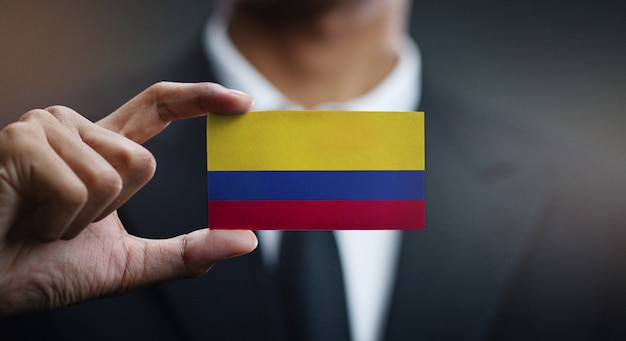 Businessman holding card of colombia flag