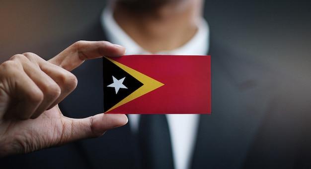 Businessman holding card of east timor flag