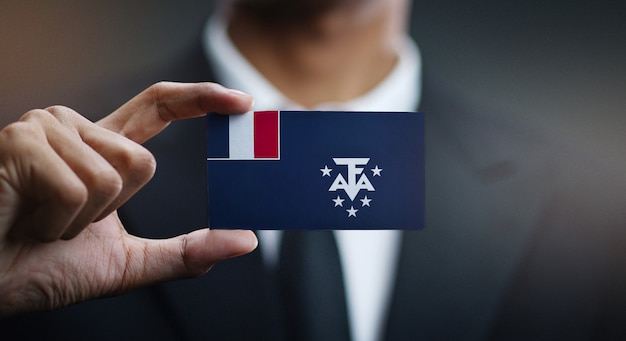 Businessman holding card of french southern flag