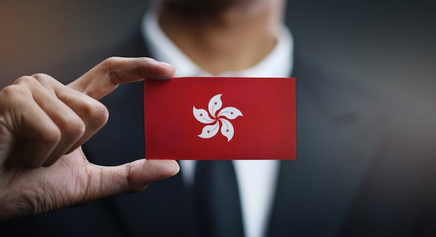 Businessman holding card of hong kong flag