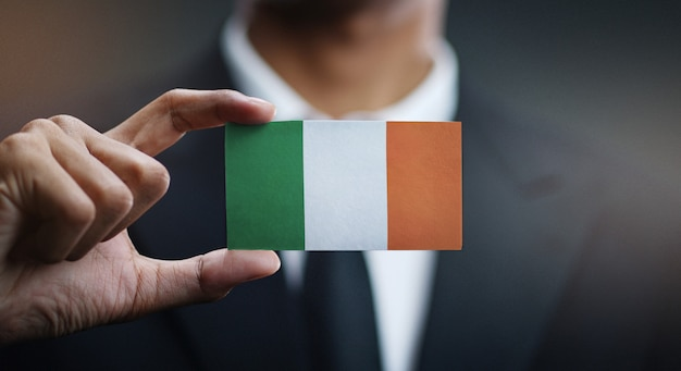 Businessman holding card of ireland flag