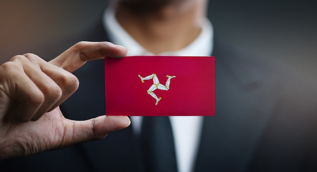 Businessman holding card of isle of man flag