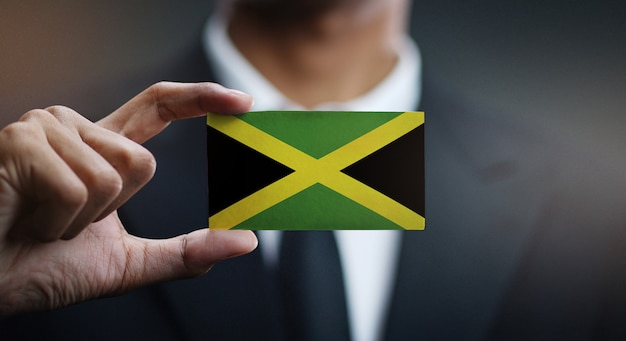 Businessman holding card of jamaica flag