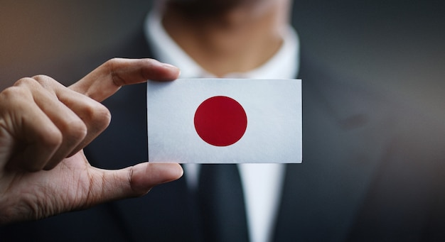 Businessman holding card of japan flag