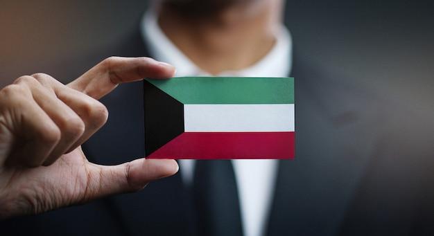 Businessman holding card of kuwait flag