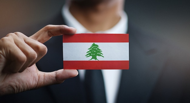 Businessman holding card of lebanon flag