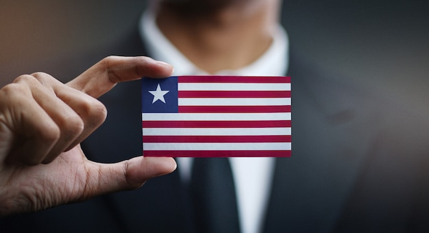 Businessman holding card of liberia flag
