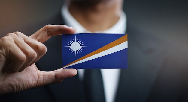 Businessman holding card of marshall islands flag