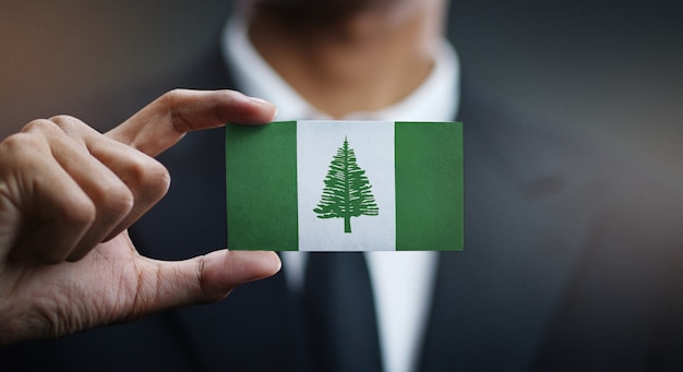 Businessman holding card norfolk island flag