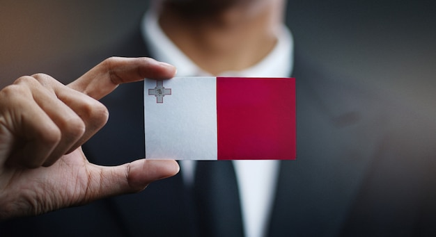 Бизнесмен, держа карты мальты флаг