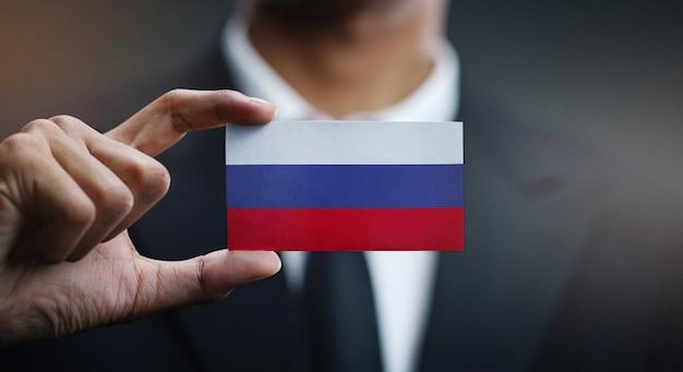 Бизнесмен, держа карты россии флаг