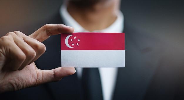 Businessman holding card of singapore flag