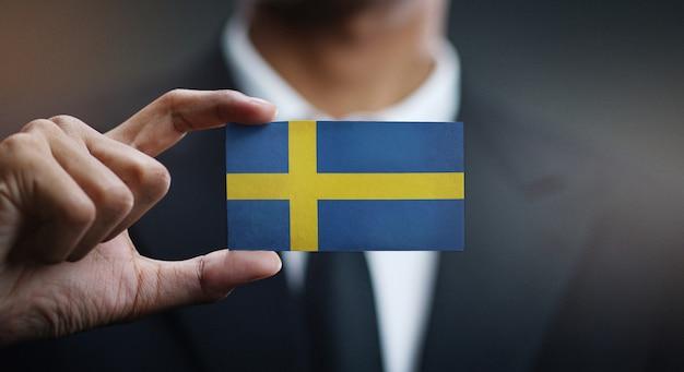 Businessman holding card of sweden flag
