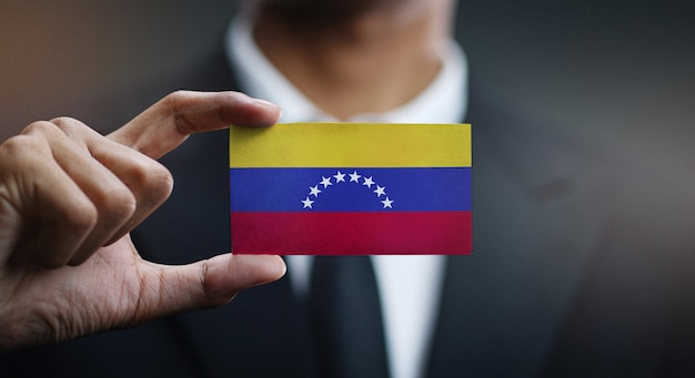 Businessman holding card of venezuela flag