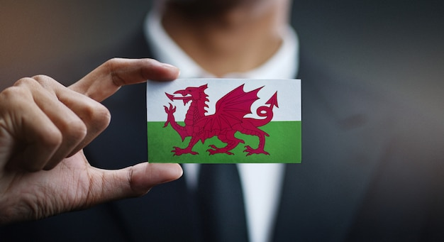 Businessman holding card of wales flag