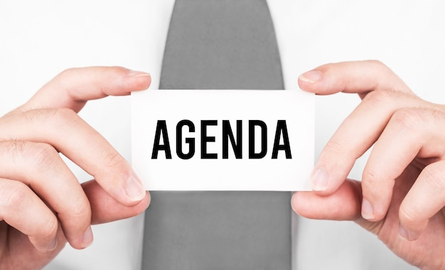 Businessman holding a card with text agenda , business concept