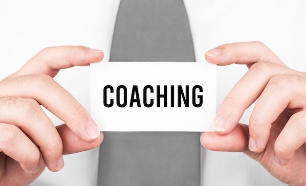 Businessman holding a card with text coaching,business concept