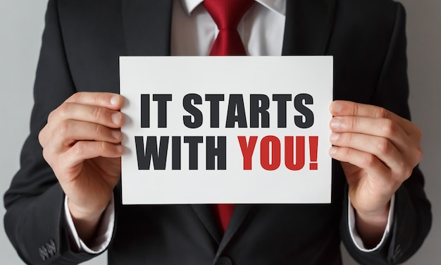 Businessman holding a card with text it starts with you