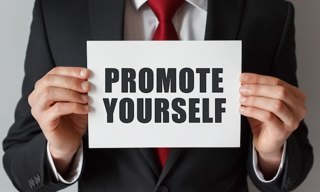 Businessman holding a card with text promote yourself