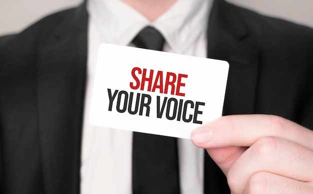 Businessman holding a card with text share your voice