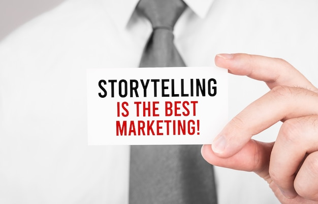 Businessman holding a card with text storytelling is the best marketing , business concept