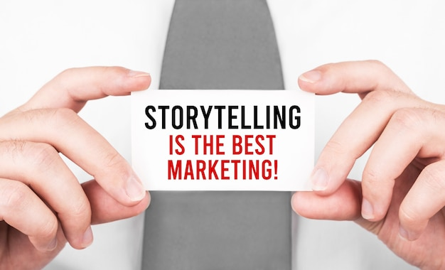Businessman holding a card with text storytelling is the best marketing ,business concept