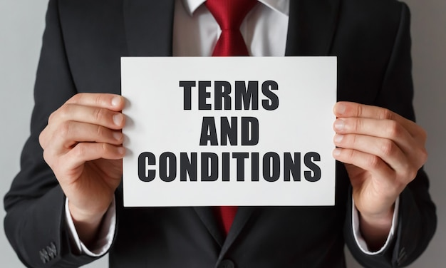 Businessman holding a card with text terms and conditions