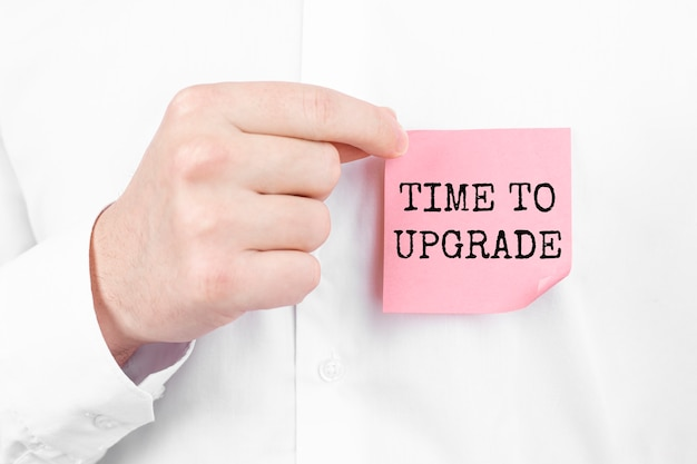 Businessman holding a card with text time to upgrade ,business concept