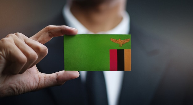 Businessman holding card of zambia flag