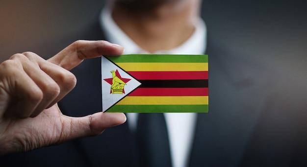 Businessman holding card of zimbabwe flag