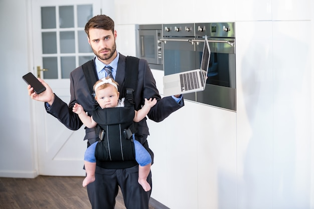 Businessman holding cellphone and laptop while carrying daughter
