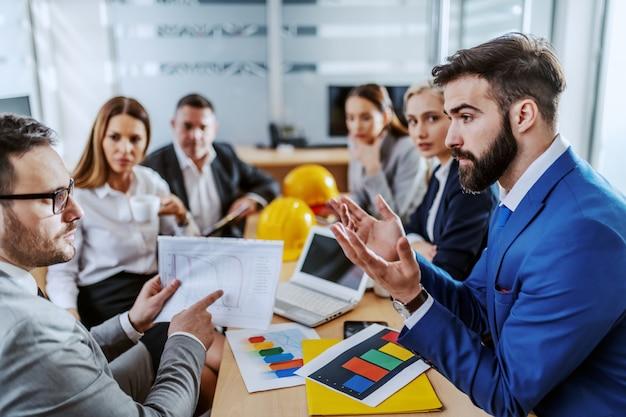 Бизнесмен, держащий диаграмму, указывая на нее и не согласный со своим коллегой. другой коллега смотрит на них и слушает. интерьер зала заседаний.