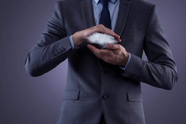 Businessman holding a cloud