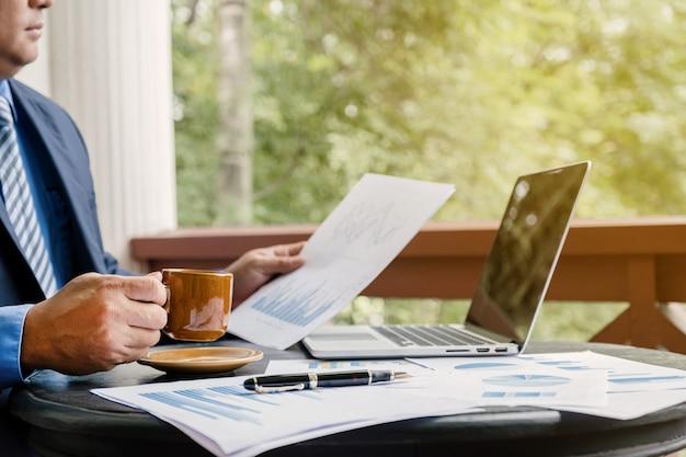 コーヒーカップを保持しているビジネスマンは、ホームオフィスでラップトップでグラフを分析します