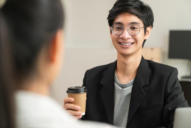 Бизнесмен, держа чашку кофе и улыбаясь во время разговора