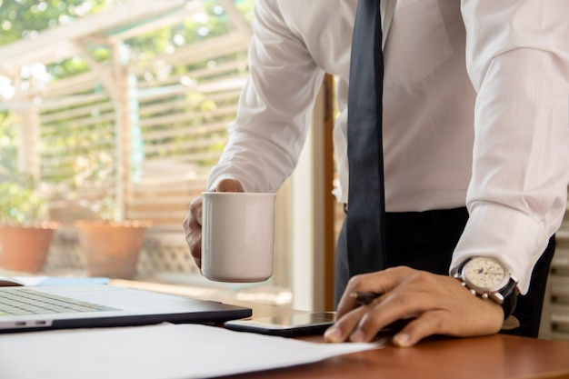 Businessman holding coffee mug  with laptop on table.