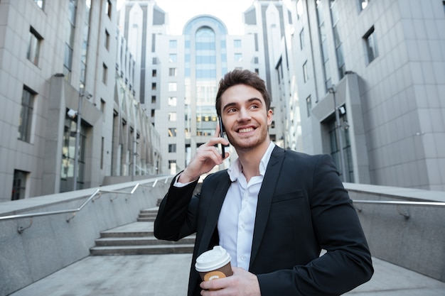 Businessman holding coffee and phone