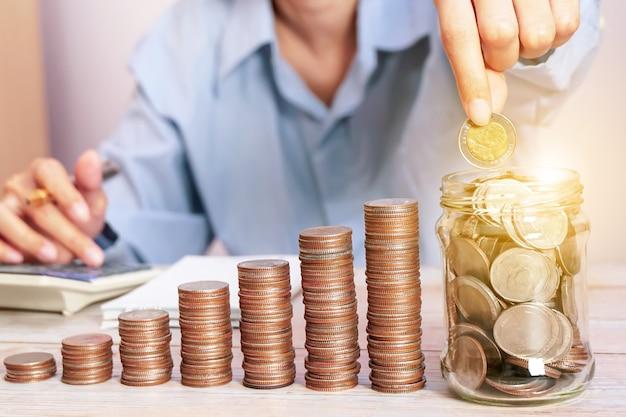 금융 회계를 위해 돈을 절약하는 glassconcept에 동전을 넣은 사업가
