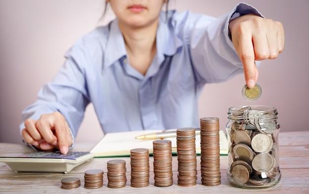 Бизнесмен, держащий монету, кладет в стеклянную концепцию экономии денег для финансового учета, экономя деньги