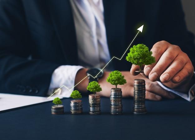 Бизнесмен, держащий монету с графом и деревом, растущим на денежной монете