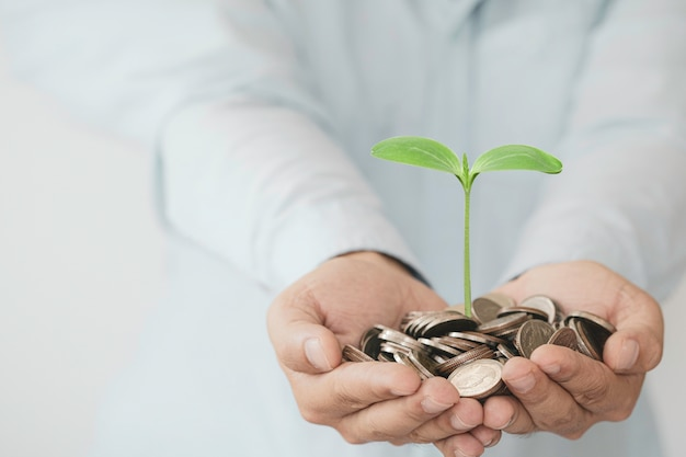 Businessman holding coins in hand with growth plant.