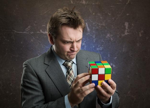 Бизнесмен, держа в руках красочный куб