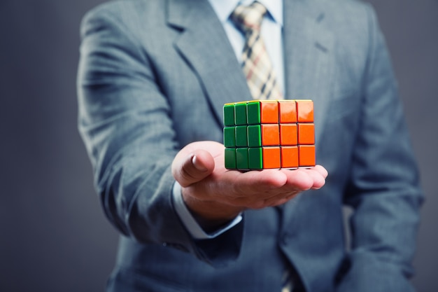 Businessman holding colorful rubik cube in his hands