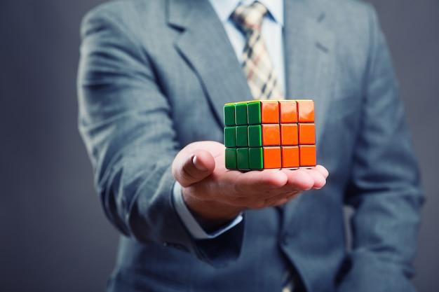 Бизнесмен, держа в руках красочный кубик рубика