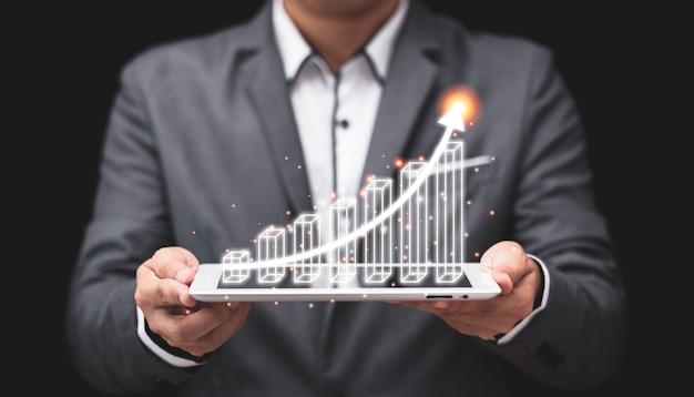 가상 막대 그래프와 증가 화살표와 함께 컴퓨터 태블릿을 들고 사업