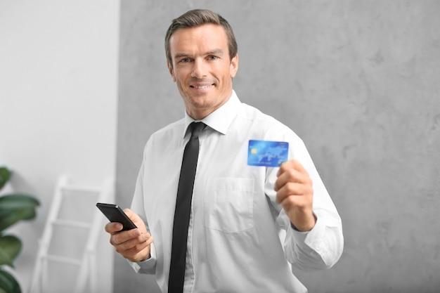 クレジットカードとスマートフォンを室内で持つビジネスマン